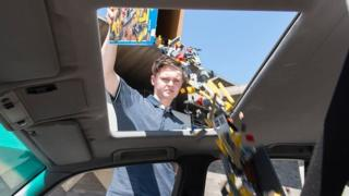 A man pours Lego into a car at a gallery in Australia