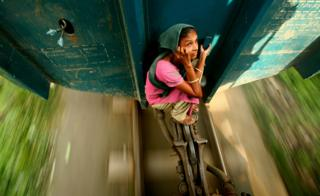 A woman travelling on the locking system of a carriage. Dhaka, Bangladesh
