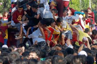 Catholics stand on each others' shoulders to try to touch the statue in Manila (9 Jan 2019)