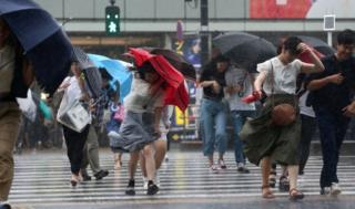 Pedestrians crossing a road struggle against the strong wind and rain in Tokyo, Japan, on 28 July 2018