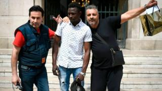 A 22-year old Mamoudou Gassama from Mali (C) poses with passers-by in front of the town hall of Montreuil, an eastern Paris suburb, on May 28, 2018
