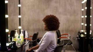 hollywood Woman sits in the mirror looking at her curly afro hairstyle