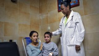 Cuban PhD in oncology Migdalia Perez (R) stands next to 6-year old cancer patient Noemi Bernardez and her mother Elizabeth Navarro (L) at the Cancer Hospital of Havana, 26 Oct 2015
