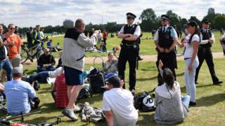 Police speak to a large group gathered in a park in central London