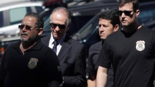 The President of the Brazilian Olympic Committee pictured between federal officers, wearing a suit and sunglasses
