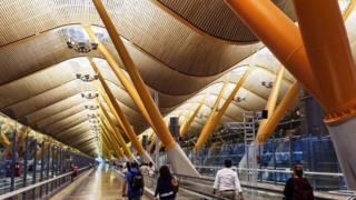 Pessoas caminham em corredor de aeroporto