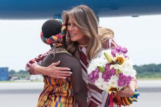 US First Lady Melania Trump receives flowers during an arrival ceremony after landing at Kotoka International Airport in Accra October 2, 2018 as she begins her week long trip to Africa to promote her 'Be Best' campaign.
