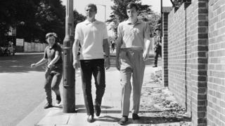 An eager young football fan chases England footballers Bobby Moore and Martin Peters as they stroll near the team's hotel in Hendon, London, on 23 July 1966. (Photo by Central Press/Hulton Archive/Getty Images)