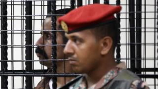 Maarik al-Tuwayha stands behind bars during his trial, for the killing of three American military trainers outside an army base last year, on July 17, 2017