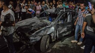 Onlookers gather around a charred car