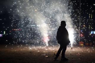 A man walks past fireworks in the street outside an apartment building in Beijing early on 8 February 2016 for the Lunar New Year celebrations which marks the start of the year of the monkey.
