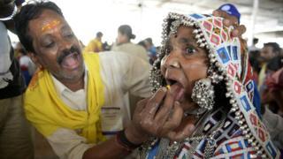 """Индийский лекарь в городе Хайдарабад кормит пациентку """"рыбьим препаратом"""", то есть живой рыбой, которую местные племена считают традиционным средством от астмы."""