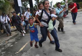 Mulher corre com os filhos em meio à confusão na fronteira entre México e Guatemala
