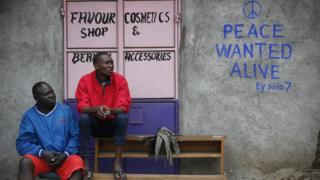 Men sit in front of a wall with a message of peace painted recently by local street artist Solomon Muyundo in Kibera, Nairobi