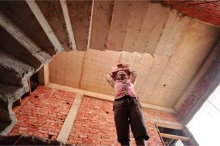 Ram Bhavan at a construction site carrying bricks