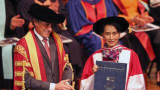 Nobel Peace Laureate and Myanmar opposition leader Aung San Suu Kyi (R) is presented with a degree of Doctor of Laws by Monash University Chancellor Dr Alan Finkel at Monash University in Melbourne on November 30, 2013.