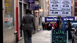 woman walks past a chip shop