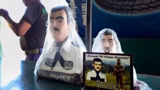 """Una foto de Joaquín """"el Chapo"""" Guzmán frente a dos figuras de Malverde en una tienda contigua a una capilla dedicada al santo en Culiacán, Sinaloa, México, el 7 de diciembre de 2016."""