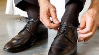 A stock image of a man doing his shoe laces