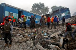 """Rescue workers search for survivors at the site of Sunday""""s train derailment in Pukhrayan, south of Kanpur city, India November 21, 2016."""