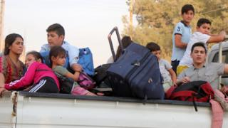 Families flee the town of Ras al-Ain in north-east Syria (10 October 2019)