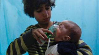 A Syrian boy holds an oxygen mask over the face of an infant