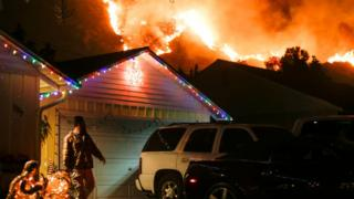A man prepares to evacuate his home as a wildfire burns along a hillside near homes in Santa Paula, California, on December 5, 2017. Fast-moving, wind-wind-fuelled brush fire exploded to about 10,000 acres in Ventura County Monday night, forcing hundreds of people to flee their homes, officials said.