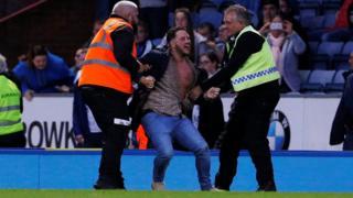 Fan taken away by police