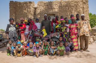 Oumar, 56 (centre) and family
