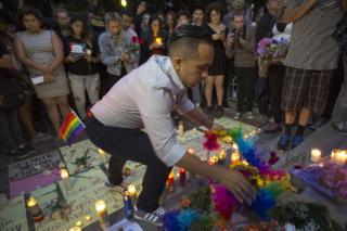 People build a makeshift memorial on the steps of City Hall during a vigil for the worst mass shooing in United States history in Los Angeles, 13 June