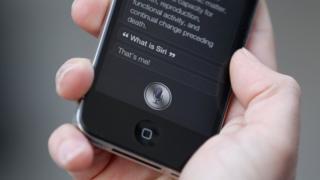 Un homme en train d'utiliser le logiciel 'Siri' sur son iPhone 4S