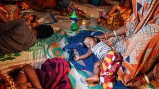 People evacuated for safety rest in a temporary cyclone relief shelter in Puri in the eastern Indian state of Odisha