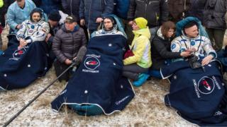 A handout photograph made available by NASA showing Russian cosmonauts Mikhail Kornienko, (L), Sergey Volkov of Roscosmos, (C), and Expedition 46 Commander Scott Kelly (R) of NASA, resting in chairs outside of the Soyuz TMA-18M spacecraft just minutes after they landed in a remote area near the town of Zhezkazgan, Kazakhstan, 02 March 2016.