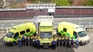 Volunteers standing in front of three ambulances