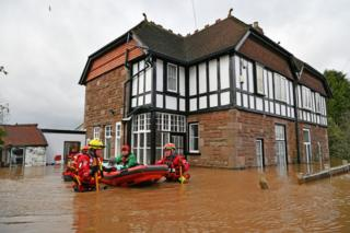 Mountain Rescue team members rescue Peter Morgan from his house which has been flooded in Monmouth.