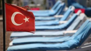 Turkish flag in front of empty sun beds