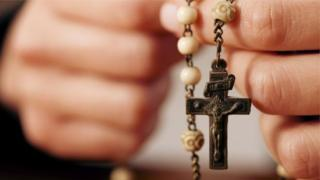 Hands holding Rosary beads