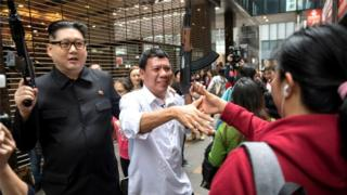 Howard X (L) and Cresencio Extreme are greeted by Filipino maids outside a Jollibee fried chicken restaurant in Hong Kong