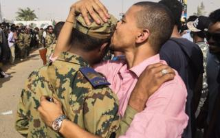 A Sudanese anti-regime protester kisses a soldier on the head during protests in Khartou, Sudan - Thursday 11 April 2019