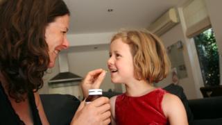 mum giving daughter a vitamin tablet