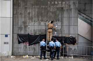香港警察总部周五晚被大批示威者包围,外墙墙面被示威者投掷鸡蛋,警方早上派人清理。