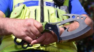 policeman holding two zombie knives