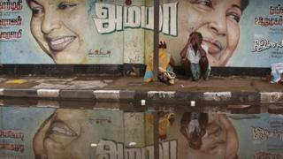A flood-affected couple sits along a flooded roadside under a picture of Jayalalithaa Jayaram, chief minister of the southern Indian state of Tamil Nadu, in Chennai, India,