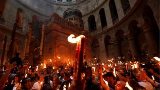 Orthodox Christians holding candles aloft in the Church of the Holy Sepulchre in Jerusalem