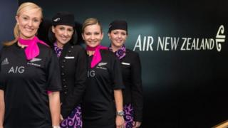 Good sports: Staff on board Australia's national carrier Qantas were all smiles when they donned the All Blacks jerseys on Monday following a social media wager