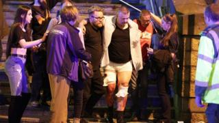 People help an injured man at the Manchester Arena