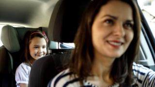 Mulher levando criança no banco de trás do carro