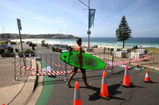 A surfer walks in front of a fence near Bondi Beach