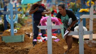 People attend a collective burial of people that have passed away due to the coronavirus disease