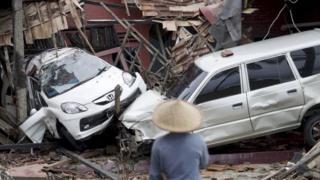 Um homem observa os destroços causados por um tsunami